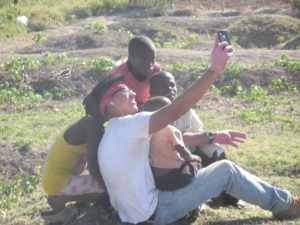 Haitians pose for a photo op on an iPhone. By Kelly Craig.
