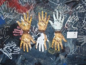 This mixed media graffiti at the East Side Gallery prompts viewers to trace outlines of their own hands.