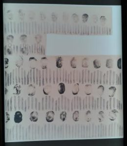 "Artwork by Jozef Szajna titled ""Our Biographies,"" with prisoners' faces depicted with their fingerprints."